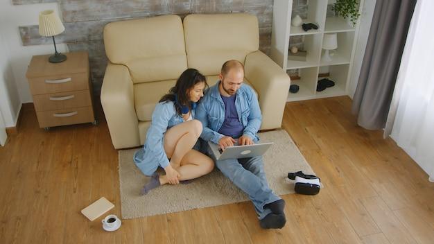 Młody mężczyzna pracuje na laptopie, podczas gdy jego kochająca żona siedzi obok niego.