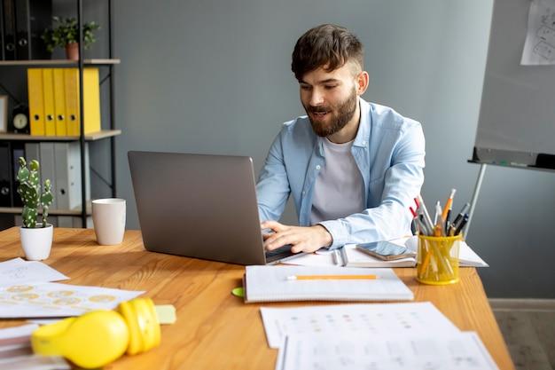 Młody mężczyzna pracuje na swoim laptopie w pracy