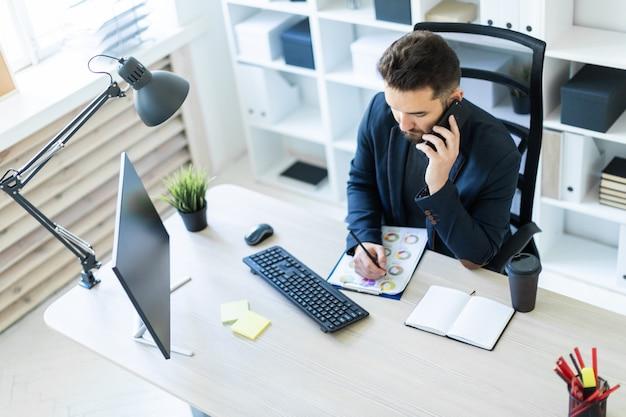 Młody mężczyzna pracuje w biurze przy biurku komputerowym z dokumentami, schematami i telefonem.