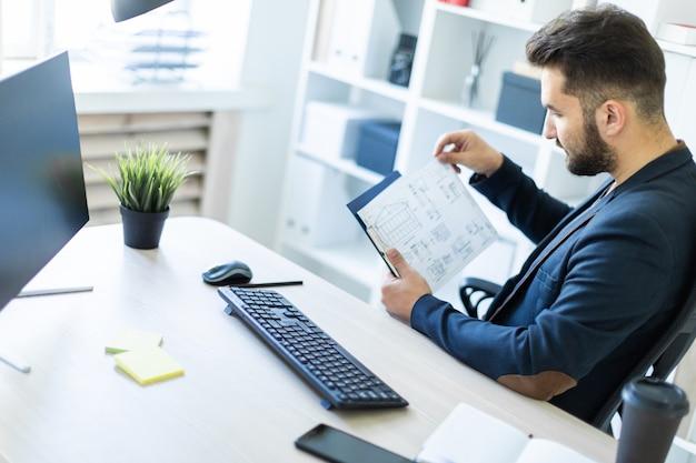 Młody mężczyzna pracuje w biurze przy biurku komputerowym z dokumentami.