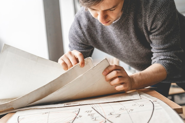 Młody mężczyzna pracuje z maketem architektury papierowej grafiki