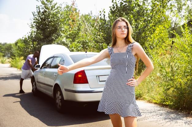 Młody mężczyzna próbuje naprawić samochód, podczas gdy młoda kobieta jedzie autostopem
