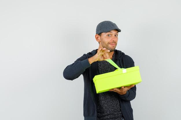 Młody mężczyzna próbuje otworzyć obecne pudełko w koszulce, kurtce, czapce i wygląda zaciekawiony. przedni widok.