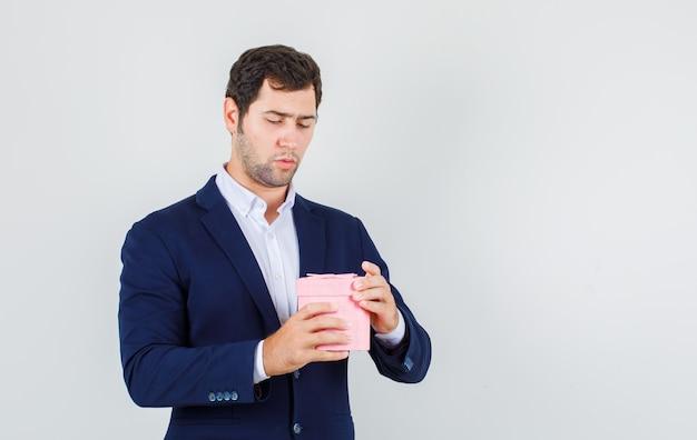 Młody mężczyzna próbuje otworzyć pudełko w garniturze i patrząc poważny, przedni widok.