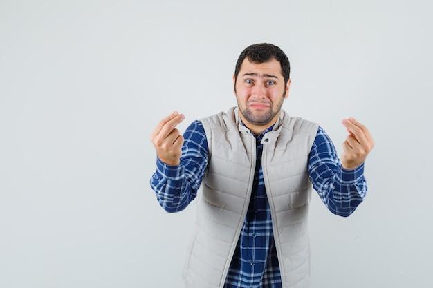 Młody mężczyzna próbuje wyjaśnić komuś coś w koszuli, kurtce i wygląda na smutnego. przedni widok.