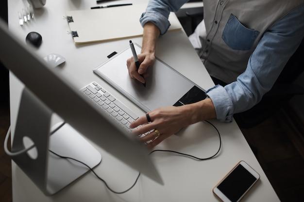Młody mężczyzna projektant za pomocą tabletu graficznego podczas pracy z com