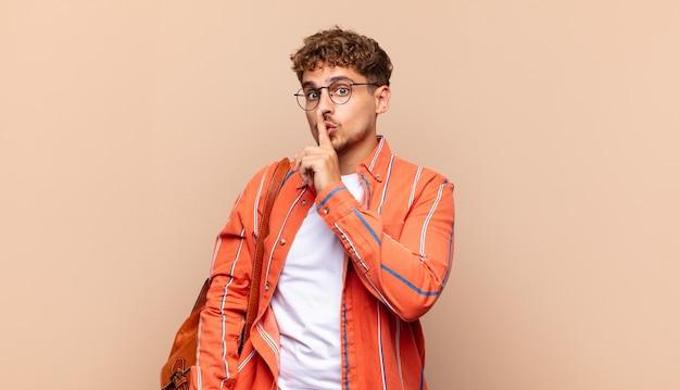Młody mężczyzna prosi o ciszę i spokój, gestykuluje palcem przed ustami, mówi cii lub zachowuje tajemnicę. koncepcja studenta