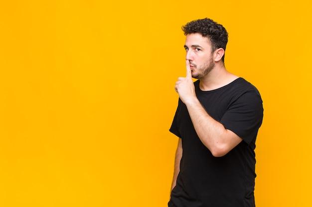 Młody mężczyzna prosi o ciszę i spokój, gestykuluje palcem przed ustami, mówi cii lub zachowuje tajemnicę