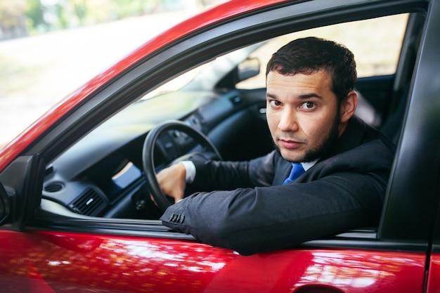 Młody mężczyzna prowadzący samochód.