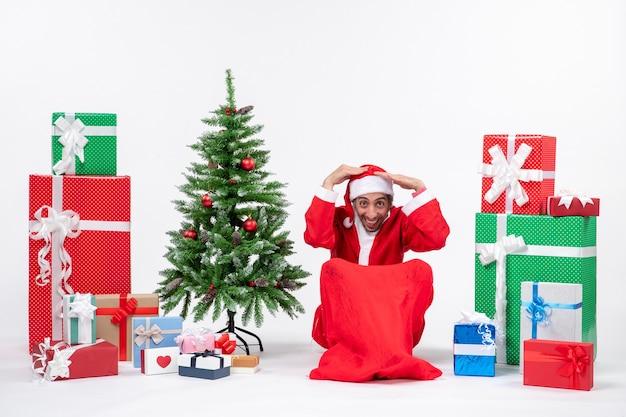 Młody mężczyzna przebrany za świętego mikołaja z prezentami i udekorowaną choinką siedzi w ziemi kładąc obie ręce