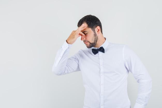 Młody mężczyzna przeciera oczy i nos w białej koszuli i wygląda na zmęczonego, widok z przodu.