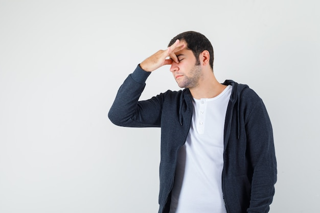 Młody mężczyzna przeciera oczy i nos w koszulce, kurtce i wygląda na zmęczonego. przedni widok.