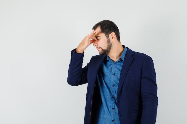 Młody mężczyzna przeciera oczy i nos w koszuli, marynarce i wygląda na zmęczonego