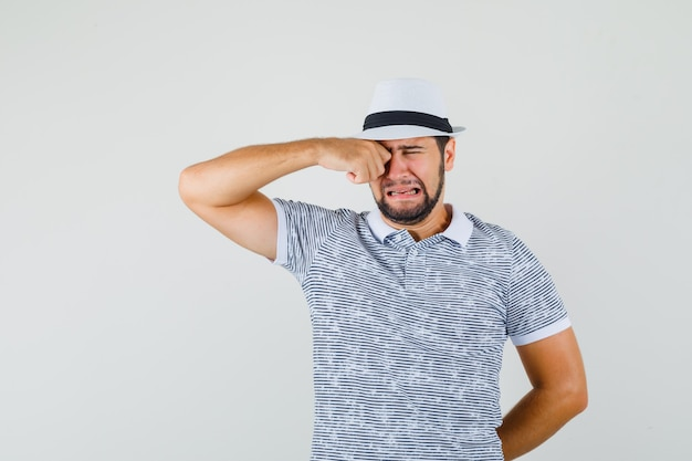 Młody mężczyzna przeciera oko płacząc jak dziecko w t-shircie, kapeluszu i wygląda na obrażonego, widok z przodu.