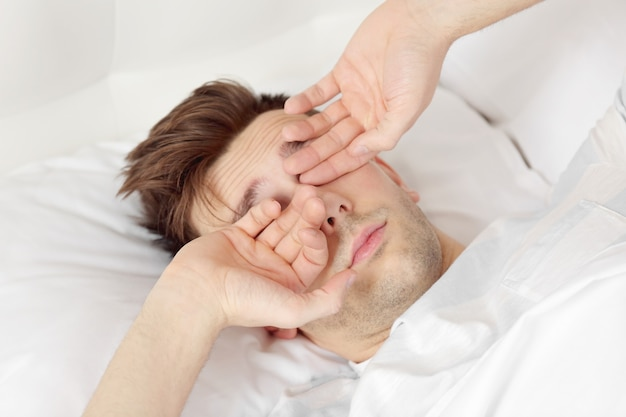 Młody mężczyzna przeciera rano oczy