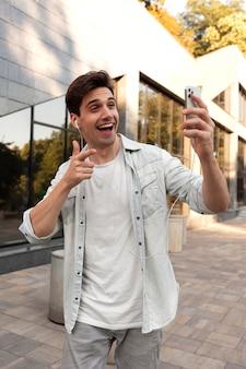 Młody mężczyzna przeprowadza rozmowę wideo na swoim smartfonie