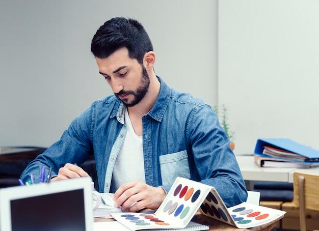 Młody mężczyzna przygotowujący nowy projekt dekoracji w przestrzeni coworkingowej