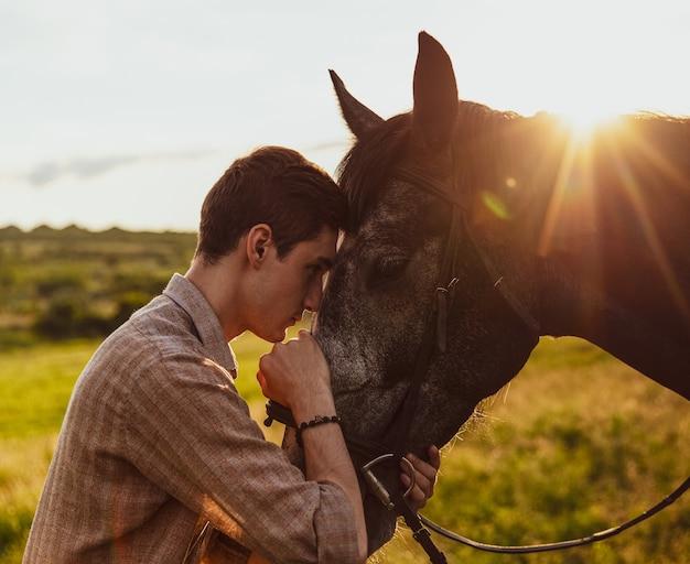 Młody mężczyzna przytula konia wieczorem na polu w słońcu