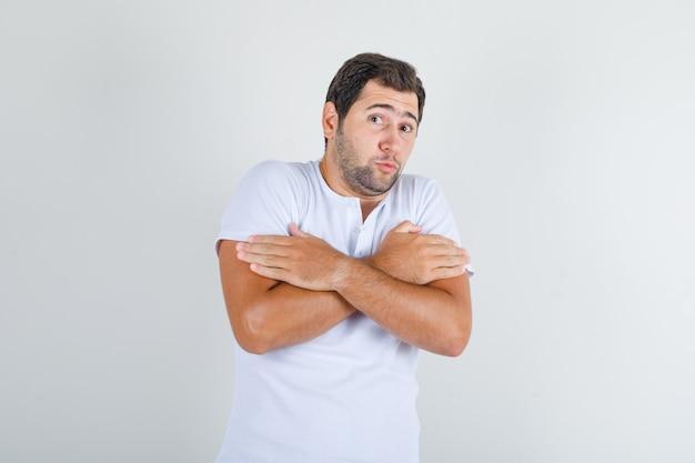 Młody mężczyzna przytulający się do rozgrzewki w białej koszulce i wyglądający ponuro