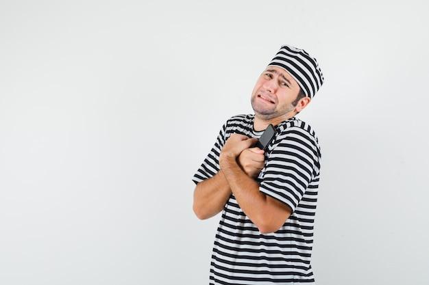 Młody mężczyzna przytulanie telefon komórkowy w koszulce, kapeluszu i żałobnym spojrzeniu. przedni widok.