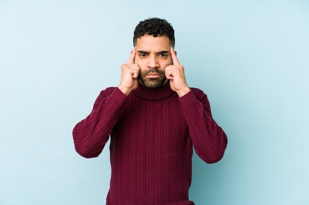 Młody mężczyzna rasy arabskiej mieszanej rasy na białym tle koncentruje się na zadaniu, trzymając palce wskazujące głową.