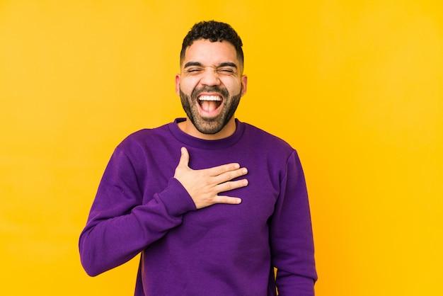 Młody mężczyzna rasy arabskiej mieszanej rasy na białym tle śmieje się głośno trzymając rękę na klatce piersiowej.