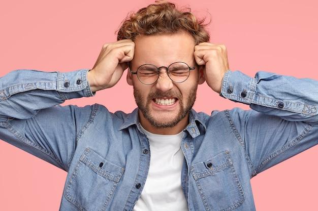 Młody mężczyzna rasy białej cierpi na bóle głowy i migrenę, trzyma pięści na skroniach, zaciska zęby, ma sfrustrowany wyraz twarzy, ubrany w dżinsową stylową koszulę, odizolowaną od różowej ściany. chory facet