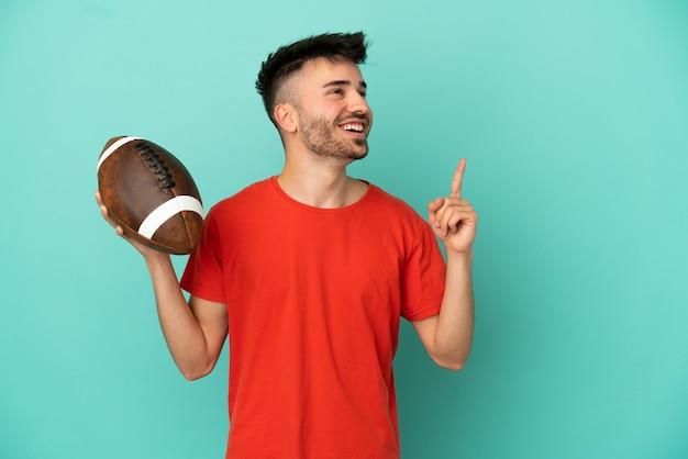 Młody mężczyzna rasy kaukaskiej grający w rugby na białym tle na niebieskim tle, wskazując na świetny pomysł