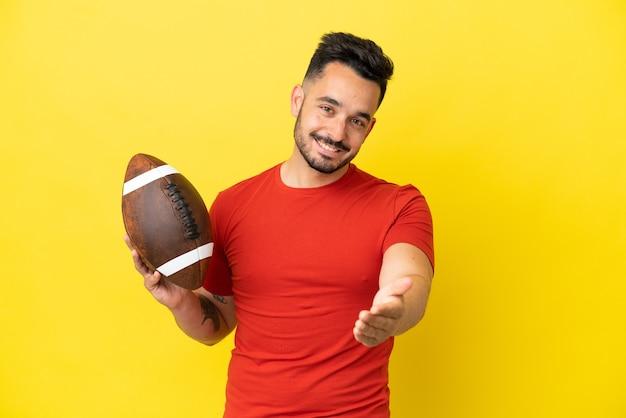 Młody mężczyzna rasy kaukaskiej grający w rugby na białym tle na żółtym tle, ściskając ręce, aby zamknąć dobrą ofertę