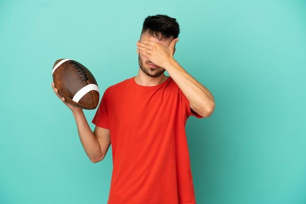 Młody mężczyzna rasy kaukaskiej gry rugby na białym tle na niebieskim tle obejmujące oczy rękami. nie chcę czegoś widzieć