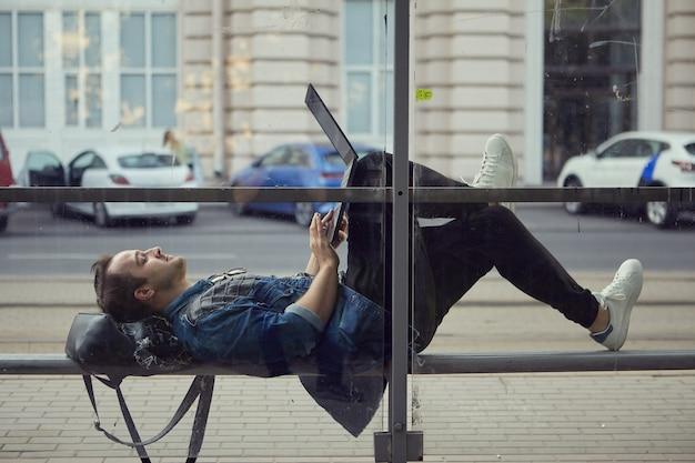 Młody mężczyzna rasy kaukaskiej na przystanku autobusowym leży na ławce z laptopem na kolanach.
