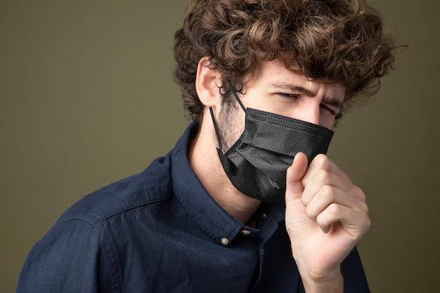 Młody mężczyzna rasy kaukaskiej noszący czarną maskę na twarz, kaszel