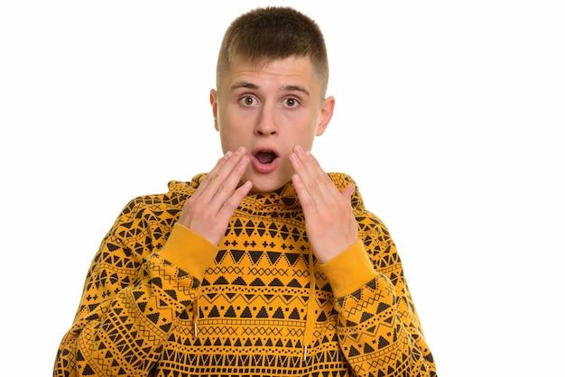 Młody mężczyzna rasy kaukaskiej, patrząc zaskoczony i zszokowany