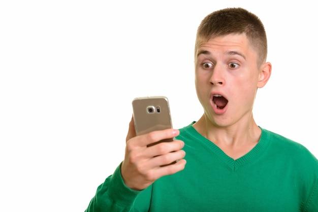 Młody mężczyzna rasy kaukaskiej posiadania telefonu komórkowego patrząc zaskoczony