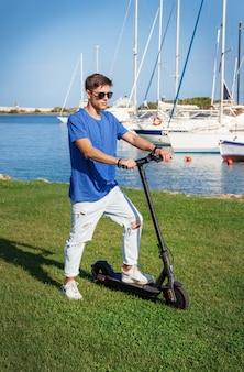 Młody mężczyzna rasy kaukaskiej pozostaje ze skuterem elektrycznym na trawie w pobliżu morza w marinie