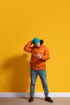 Młody mężczyzna rasy kaukaskiej przy użyciu portretu całej długości ciała smartfona nad żółtym