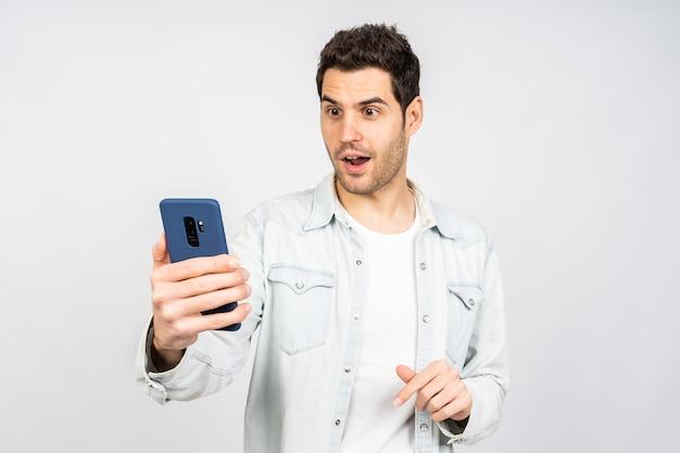 Młody mężczyzna rasy kaukaskiej robi selfie telefonem na tle białej ściany
