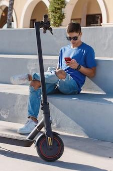 Młody mężczyzna rasy kaukaskiej siedzący na zewnątrz w pobliżu skutera elektrycznego i używający smartfona