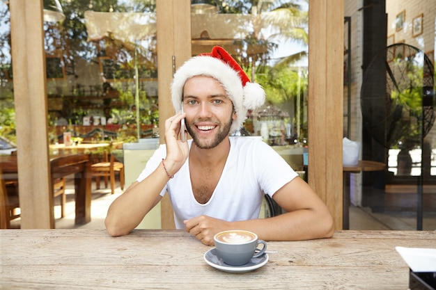 Młody mężczyzna rasy kaukaskiej szczęśliwy uśmiech atrakcyjny w czerwonym kapeluszu z białym futrem, mówiąc na telefon komórkowy ze swoimi przyjaciółmi podczas picia kawy w kawiarni