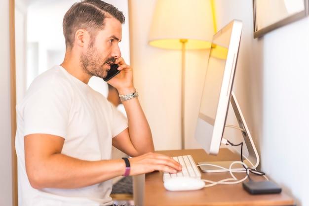 Młody mężczyzna rasy kaukaskiej telepracy w domu na komputerze