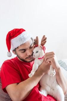 Młody mężczyzna rasy kaukaskiej w kapeluszu świętego mikołaja bawi się swoim białym kotem w rogach łosia