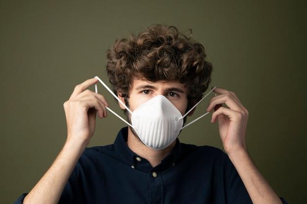 Młody mężczyzna rasy kaukaskiej zakłada jednorazową maskę ochronną