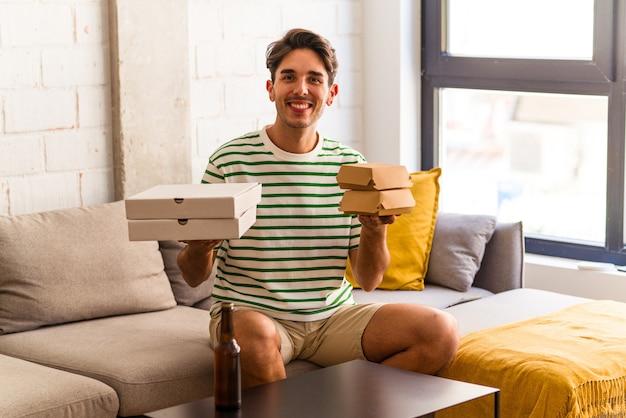 Młody mężczyzna rasy mieszanej je pizzę i burgera i pije piwo