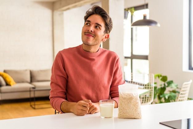 Młody mężczyzna rasy mieszanej jedzący na śniadanie płatki owsiane i mleko w swojej kuchni marzący o osiągnięciu celów i celów