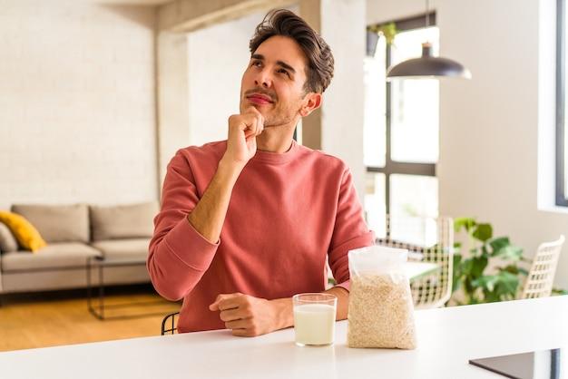Młody mężczyzna rasy mieszanej jedzący płatki owsiane i mleko na śniadanie w swojej kuchni, patrząc z boku z powątpiewaniem i sceptycznym wyrazem twarzy.