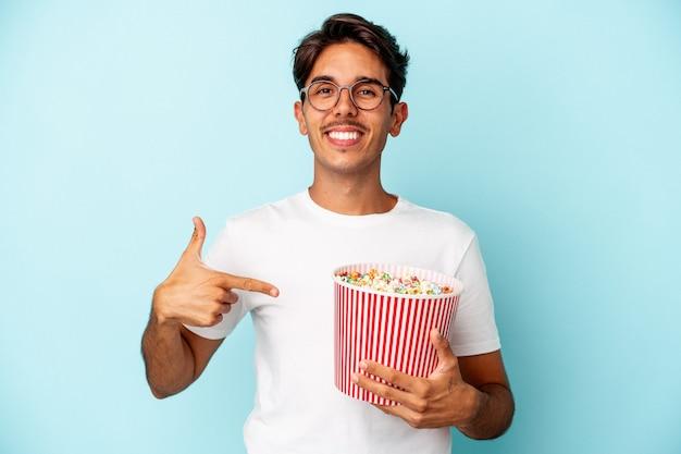 Młody mężczyzna rasy mieszanej jedzący popcorny na białym tle na niebieskim tle osoba wskazująca ręcznie na miejsce na koszulkę, dumna i pewna siebie