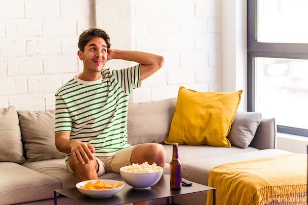 Młody mężczyzna rasy mieszanej jedzący popcorny siedzący na kanapie dotykający tyłu głowy, myślący i dokonujący wyboru.