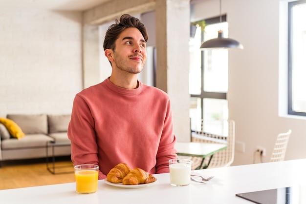 Młody mężczyzna rasy mieszanej jedzący rano śniadanie w kuchni, marzący o osiągnięciu celów i celów