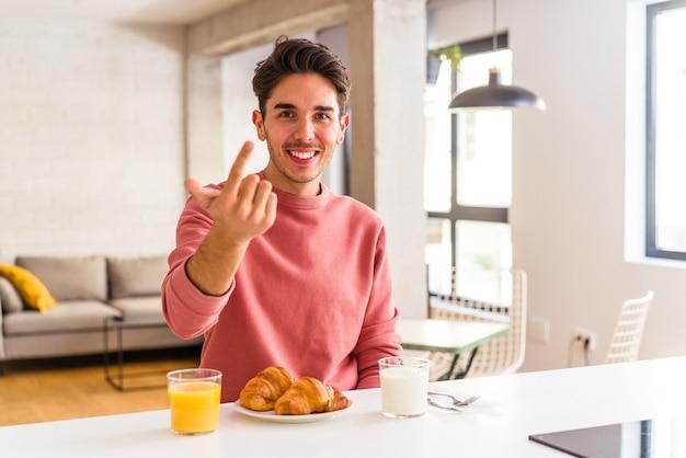 Młody mężczyzna rasy mieszanej jedzący rano śniadanie w kuchni, wskazując palcem na ciebie, jakby zapraszając podejdź bliżej.