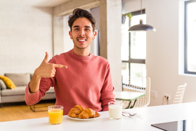 Młody mężczyzna rasy mieszanej jedzący śniadanie w kuchni rano, wskazując ręką na miejsce na koszulkę, dumny i pewny siebie